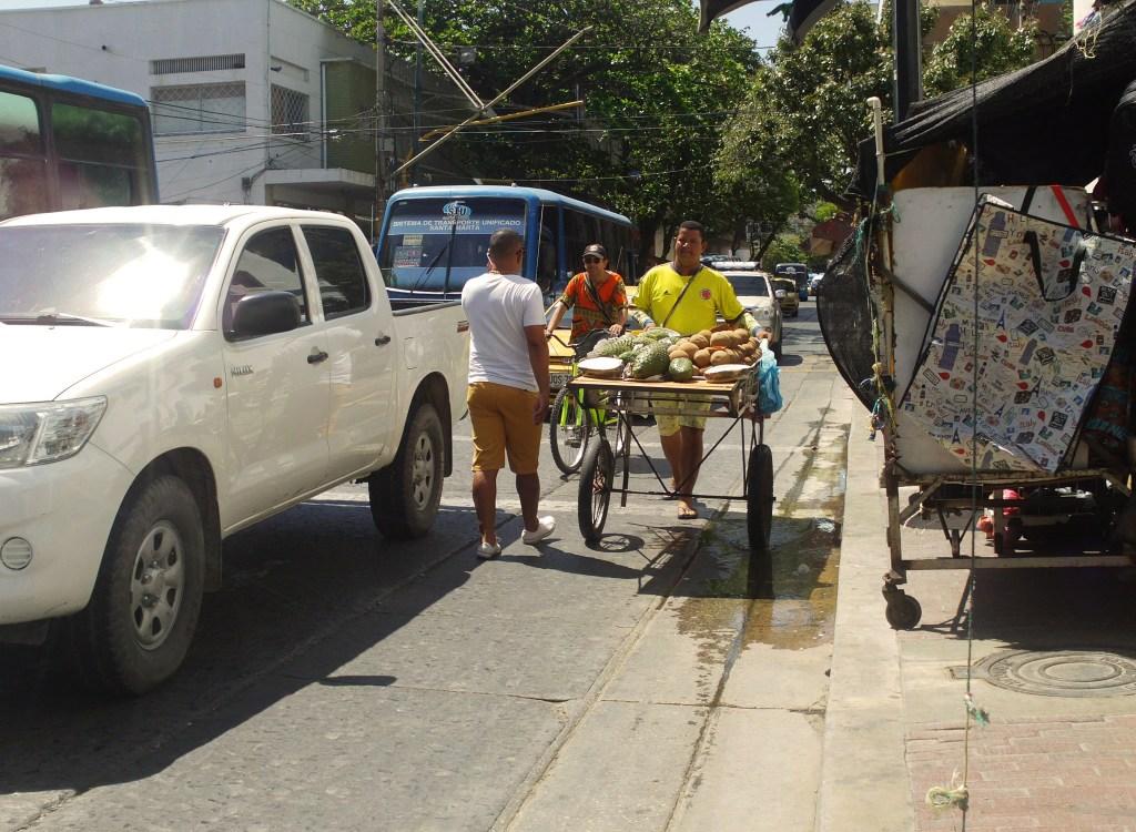 hombre vendedor conduciendo carretilla con frutas confinamiento