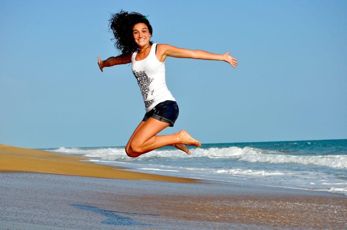 actividades mujer que salta en la playa