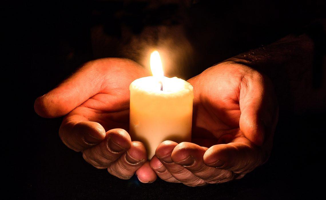 manos sosteniendo una vela