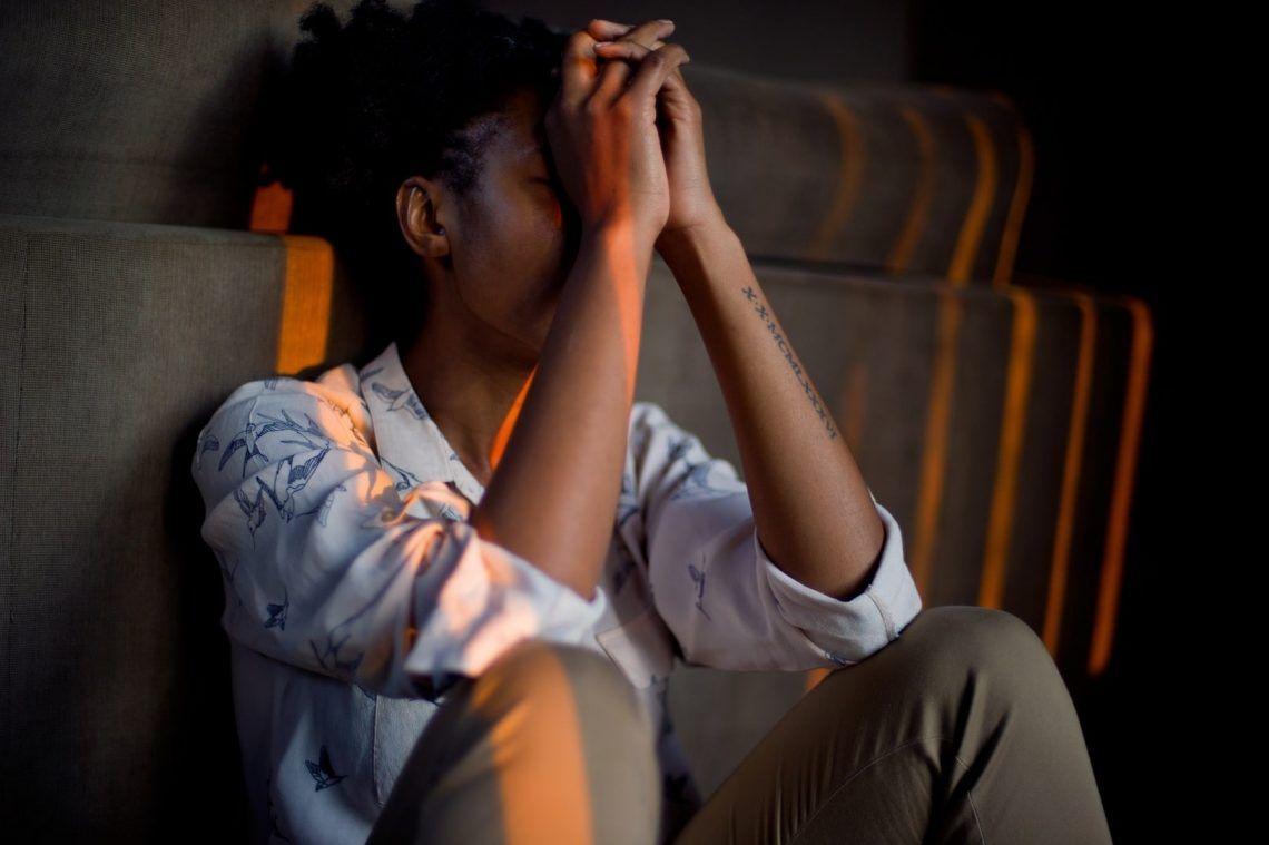 mujer triste con las mano salud mental en su rostro